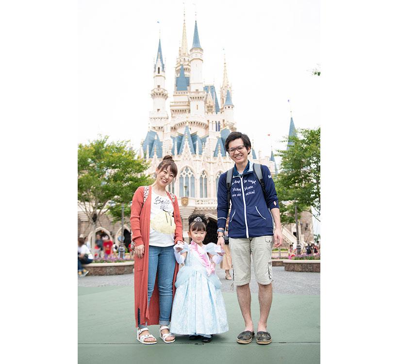 シンデレラ城前で家族3人仲良く手を繋いでいる画像