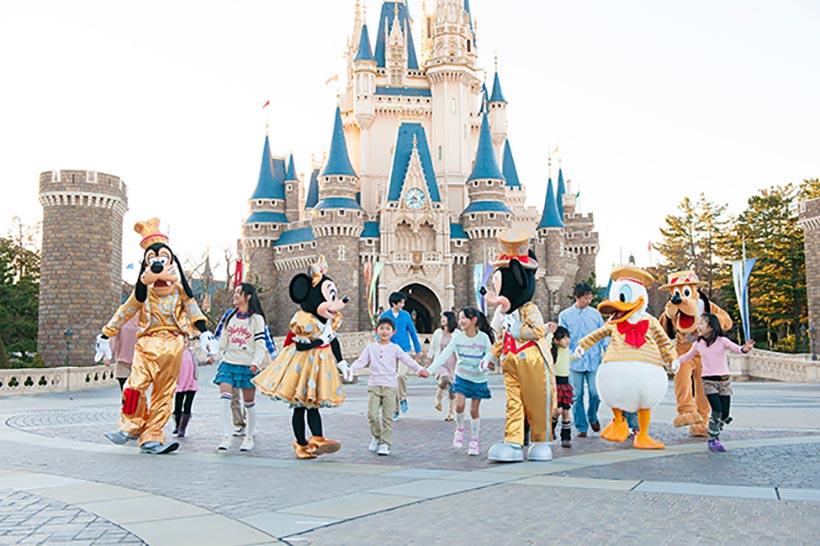 シンデレラ城の前でゲストと手をつなぐディズニーの仲間たち