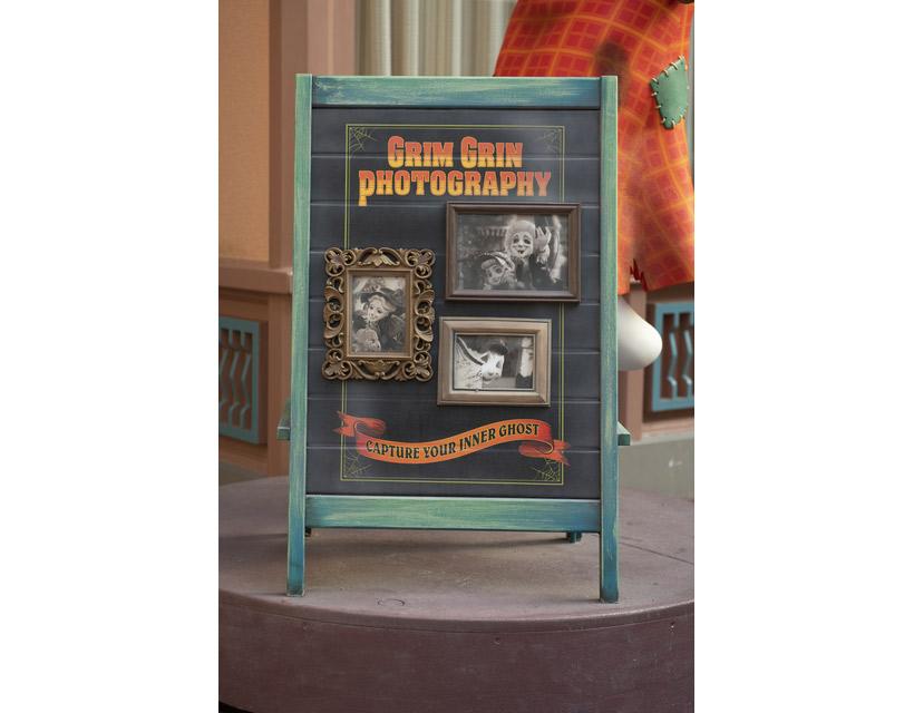 カメラを構えるゴーストが撮った写真が飾られている看板の画像