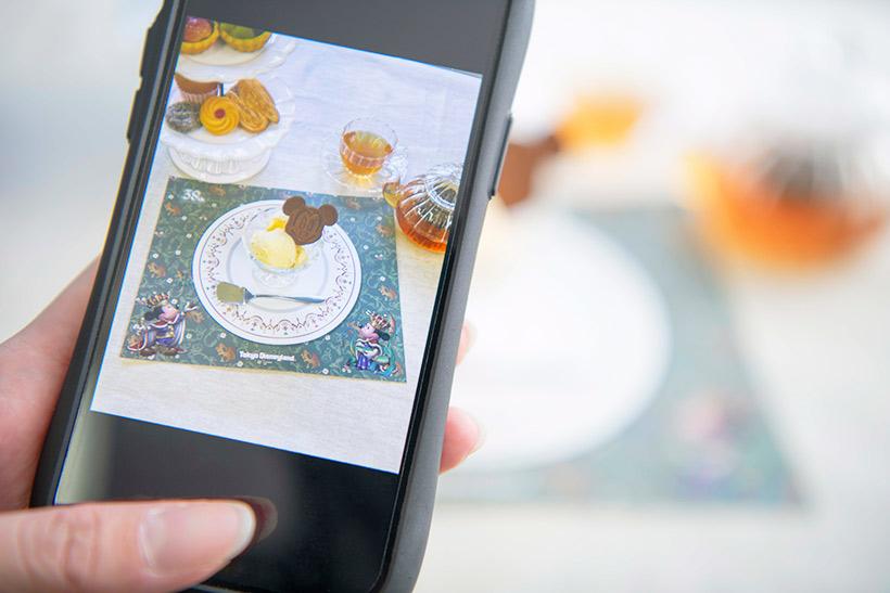 ランチョンマットとお菓子をスマホで撮影している画像