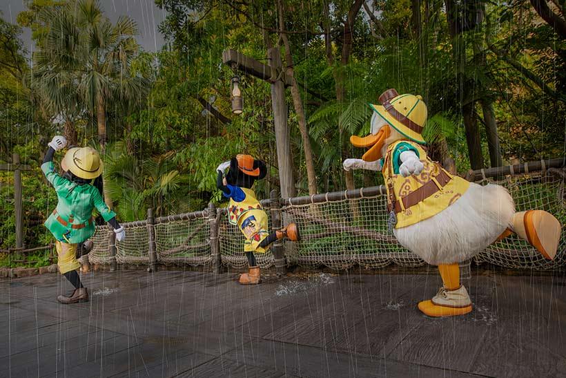 急いで雨宿りに向かうミッキーとドナルドとグーフィー