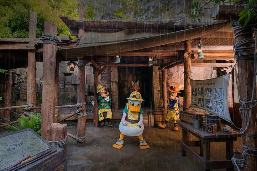 雨宿りするドナルドとミッキーとグーフィー