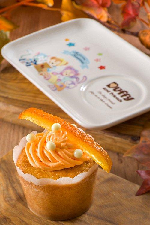 gambar オレンジの皮がアクセントになっているアーモンドマフィン(カスタードクリーム入り)。スーベニアプレートは、ダッフィーたちが描かれている横にアーモンドマフィンがぴったりフィットす...