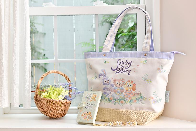 image of 花冠をつくったり、春のおとずれを楽しんでいるダッフィーたちがデザインされたトートバッグと、スマートフォンケース。 春のコーディネートとあわせて使えば、よりはなやかに♪...